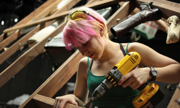 Woman with a drill building theatre sets.
